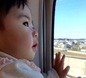 新幹線の車内から外をのぞく子供