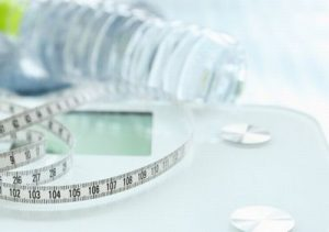 メジャーと体重計とペットボトルの水